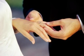Close-up of a groom placing a ring on his bride's finger